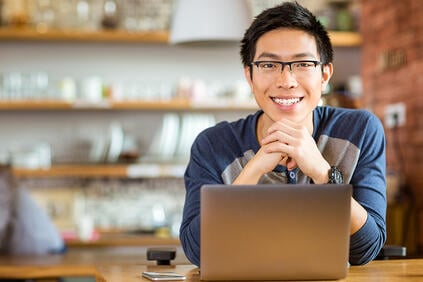 Portrait of positive asian male in glasses with laptop in cafe