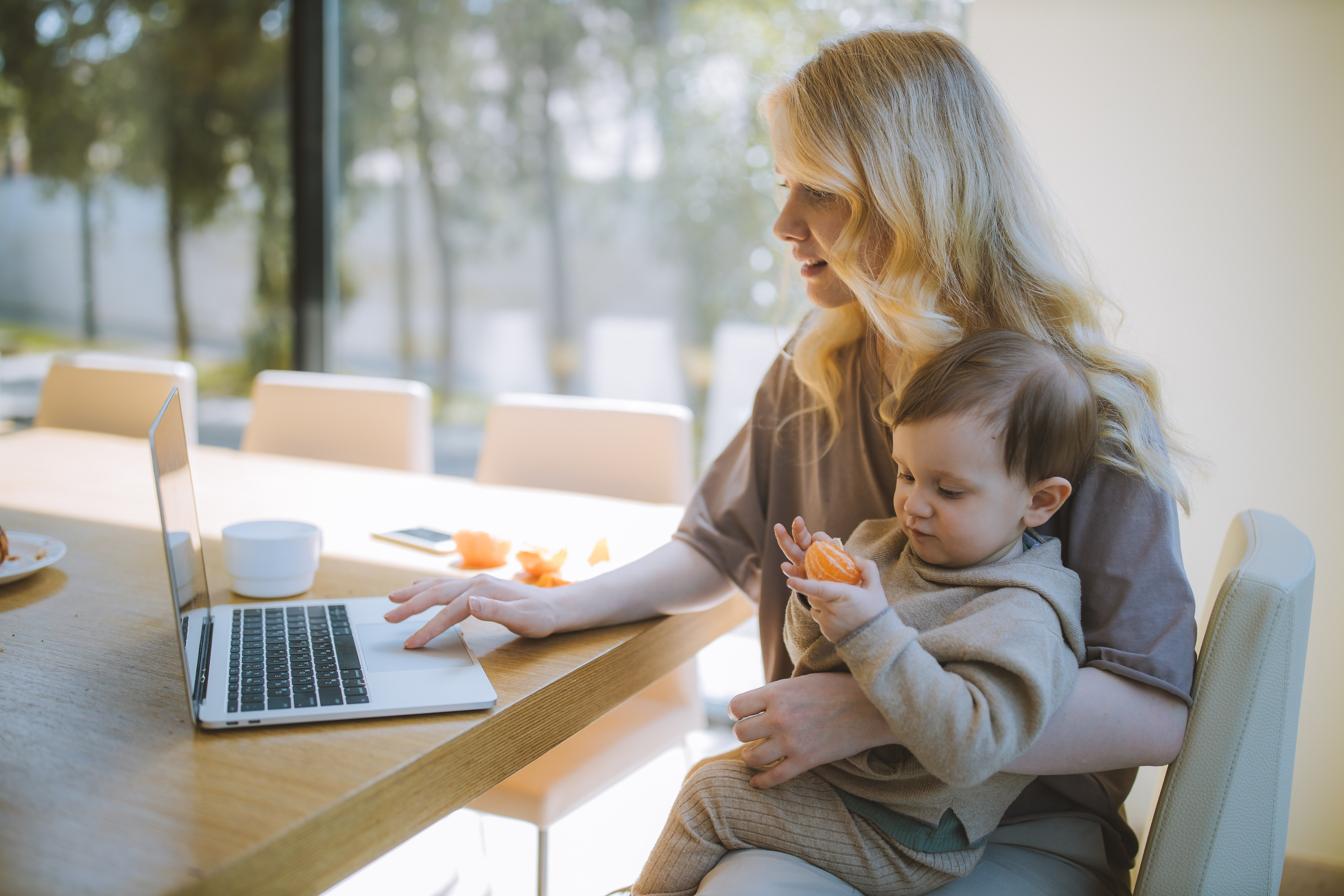 woman-carrying-her-baby-and-working-on-a-laptop-4079281